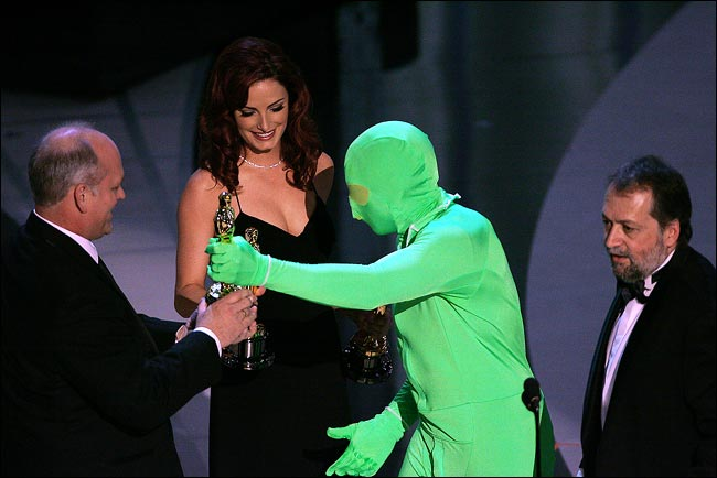 Man dressed in green suit presenting an Academy Award