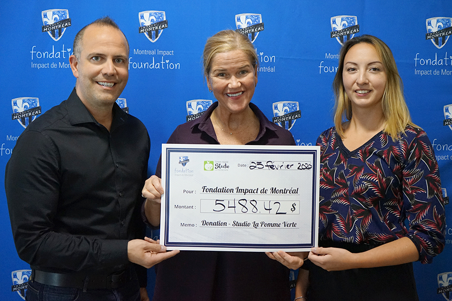 Giving check to Montreal Impact Foundation