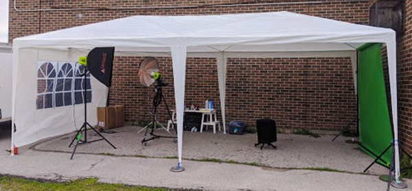 Outdoor green screen photo setup under a white tent