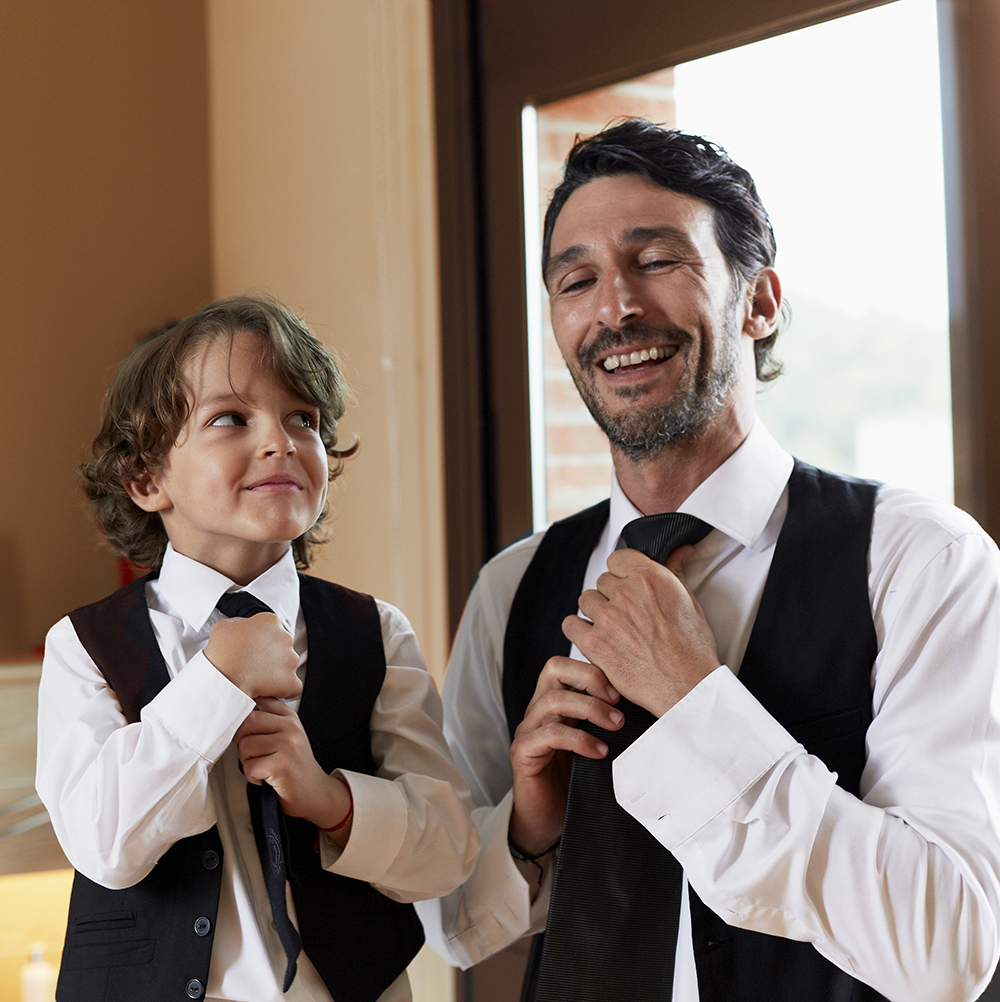 Son copying father in putting on a tie