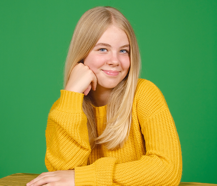 Blonde girl in yellow sweater with a green screen backdrop